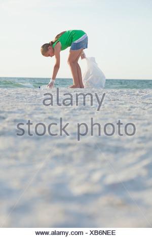 USA, Floride, Saint-Pétersbourg, Girl (10-11) nettoyage beach Banque D'Images