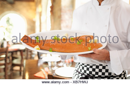 Chef holding plate of salmon Banque D'Images