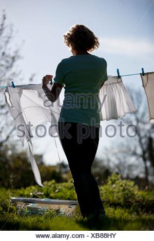 A mature woman laying sur un fil a linge, vue arrière Banque D'Images