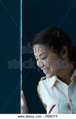 Femme regardant par la fenêtre étroite, smiling Banque D'Images