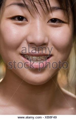 Portrait d'une jeune femme à bretelles sur ses dents Banque D'Images