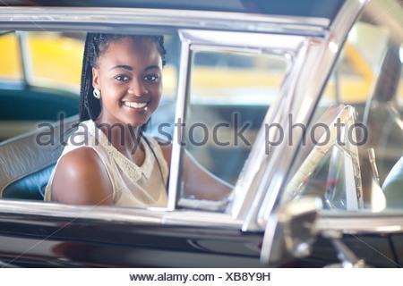 Femme en coiffure tressée roulant vintage car Banque D'Images