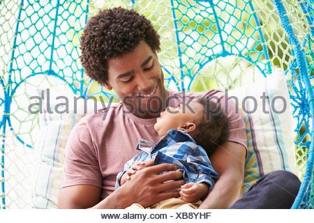 Avec Père Fils Bébé Détente sur un jardin extérieur siège pivotant Banque D'Images