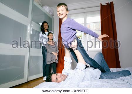 Père et fils jouant sur le lit Banque D'Images
