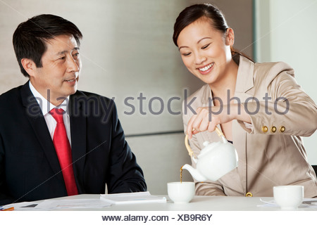 Businesswoman pouring tea for businessman Banque D'Images