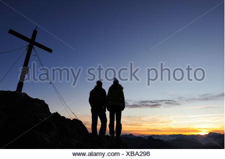 Jeune femme et jeune homme profitant de coucher de soleil au sommet des Préalpes bavaroises, Risserkogel Mangfall, Montagnes, Bavière, Allemagne Banque D'Images
