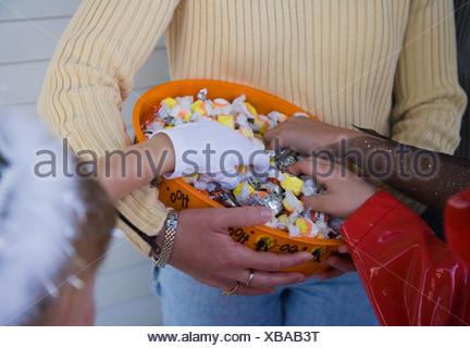 Les enfants en costumes de Halloween d'atteindre dans le bol de bonbons Banque D'Images