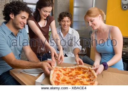 Les amis partageant une pizza Banque D'Images