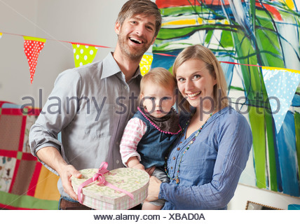 Family holding heart shaped box Banque D'Images