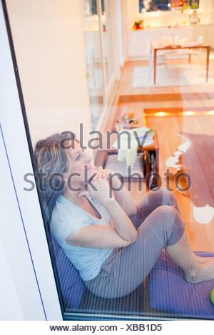 Femme assise détendue sur une fenêtre Banque D'Images