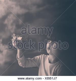 Portrait of a boy playing with toy plane Banque D'Images