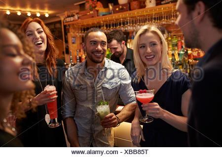 Réunion du Groupe des amis pour prendre un verre en soirée au bar à cocktails Banque D'Images