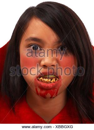 Girl constitué comme un vampire avec dents de travers et la bouche sanglante Banque D'Images