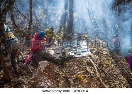 Deux membres de l'expédition manger un repas tandis que d'autres eux-mêmes occupés autour du camping. Banque D'Images