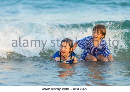 Deux enfants jouant dans la mer Banque D'Images