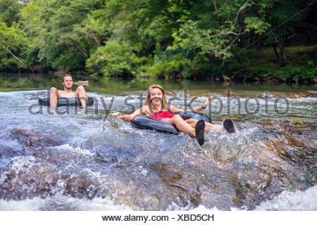 Un jeune couple tuyaux le long d'une rivière. Banque D'Images