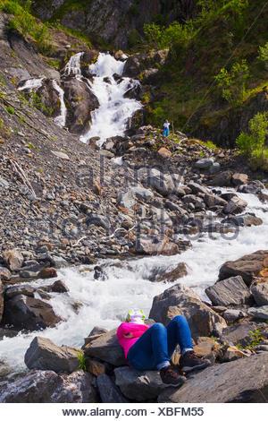 Une femme prenant une pause de kayak de mer dans le Parc National de Kenai Fjords se détend en un flux de précipitation alors que son partenaire explore une cascade