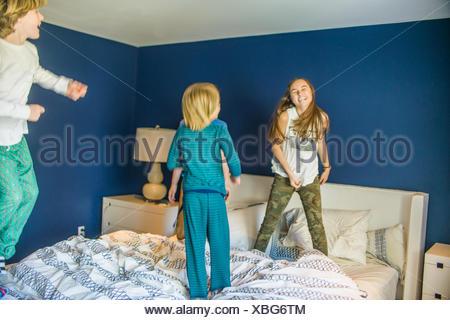 Teenage girl jumping on lit avec ses jeunes frères Banque D'Images