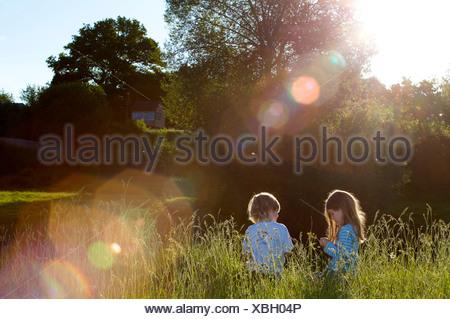 2 jeunes enfants assis dans l'herbe haute. Banque D'Images