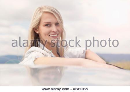 Young woman smiling à côté de voiture Banque D'Images