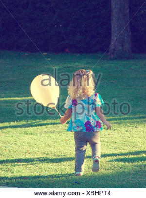Fille courant dans le parc tenant un ballon, Buenos Aires, Argentine Banque D'Images