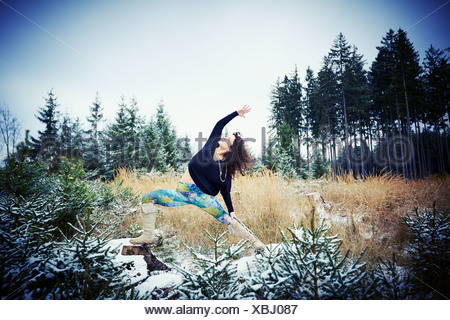 Mid adult woman practicing yoga in forest Banque D'Images
