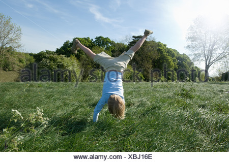 Boy doing handstand in field Banque D'Images