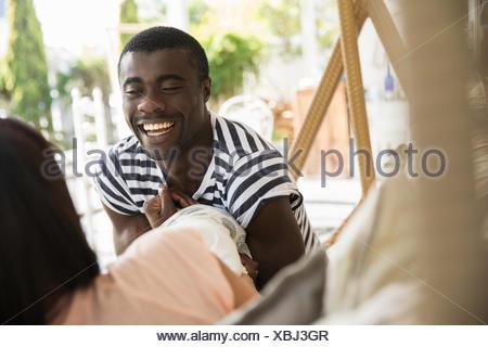 Plus d'épaule du jeune couple chatting on lit de jardin Banque D'Images