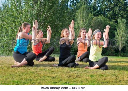 Adolescentes et tuteur sitting on grass doing yoga