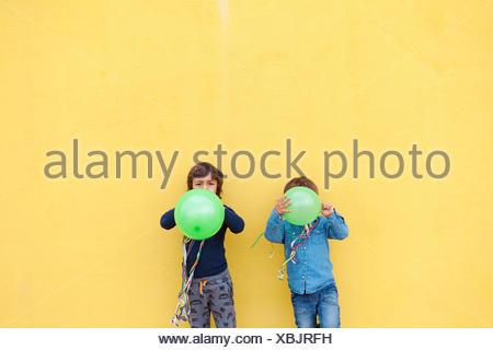 Deux petits garçons avec des ballons verts et banderolles debout devant mur jaune Banque D'Images