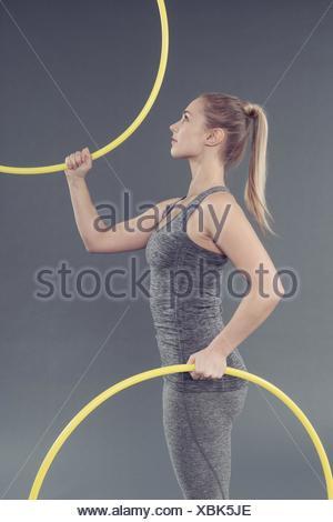 Jeune femme pratiquant avec hula hoop, fond gris Banque D'Images