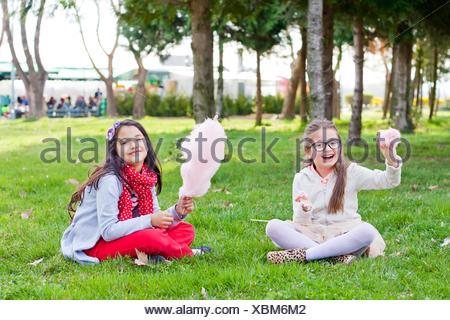 Deux filles assis dans un parc de manger de la barbe à papa Banque D'Images