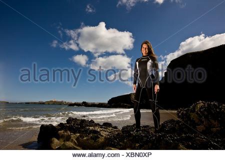Femme debout dans surfer wetsuit at waters edge, smiling Banque D'Images