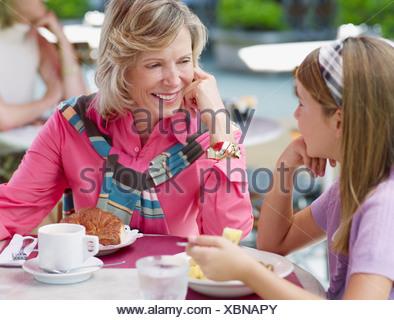 Femme et de la jeune fille sur le patio extérieur repas manger Banque D'Images