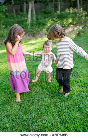Female toddler with boy and girl in garden Banque D'Images