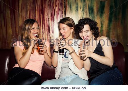 Trois amis femelles adultes de l'alcool au bar Banque D'Images