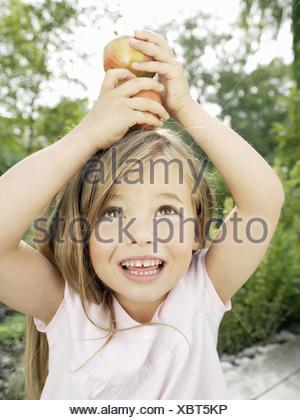 Jeune fille sur la tête des pommes d'équilibrage Banque D'Images