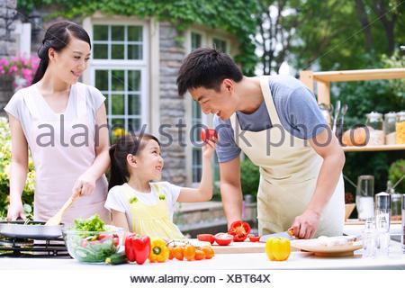 Une famille heureuse de trois dans la cuisine extérieure Banque D'Images
