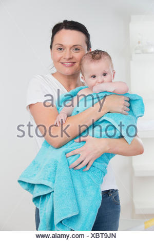 Smiling mother holding baby wrapped in a towel Banque D'Images