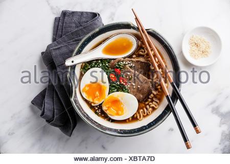 Le miso Ramen nouilles asiatiques avec le boeuf et l'oeuf dans un bol sur fond de marbre blanc Banque D'Images