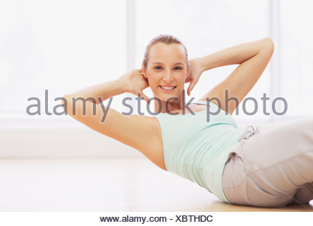 Portrait of smiling woman doing sit-ups Banque D'Images