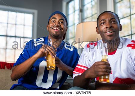 Deux amis de boire la bière en bouteille tout en regardant la télévision de canapé Banque D'Images