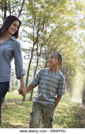Une femme et un jeune garçon tenant la main la marche dans les bois. Banque D'Images