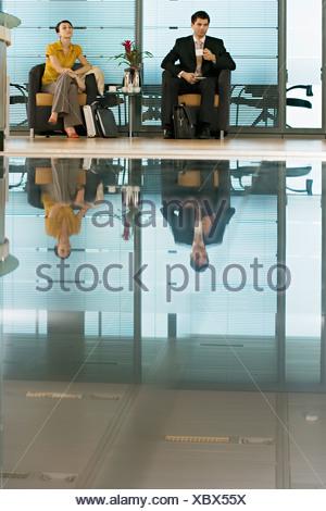 Businessman and businesswoman sitting in lobby man holding cup réflexion sur marbre brillant Banque D'Images