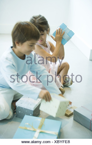 Des enfants assis sur le plancher picking up présente Banque D'Images