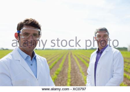 Les scientifiques standing in field Banque D'Images