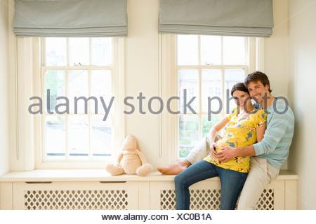 Jeune couple on windowsill, man embracing pregnant woman, smiling, portrait Banque D'Images