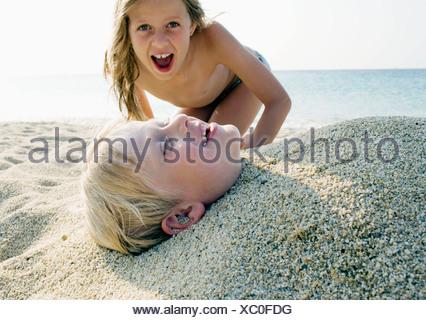 Jeune fille enterrement jeune garçon dans le sable à la plage . Banque D'Images