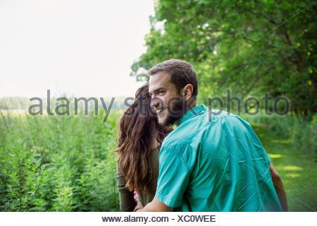 Un homme et une femme marchant dans un pré, à travers l'herbe longue sur une journée d'été. Banque D'Images
