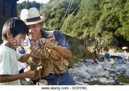 Père et fils la pêche par un ruisseau. Banque D'Images